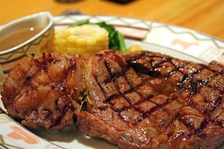 garnishing: Big thick steak with garnishing corn and gravy