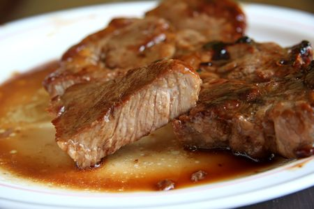 Cooked pork chop on a plate cut medium well done photo