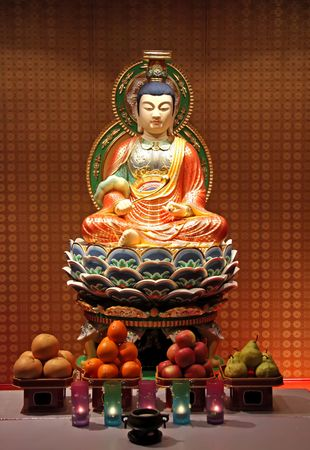 Buddha statue in chinese temple altar with offerings photo