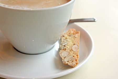 foamy: Foamy milk coffee in round cup with biscotti Stock Photo