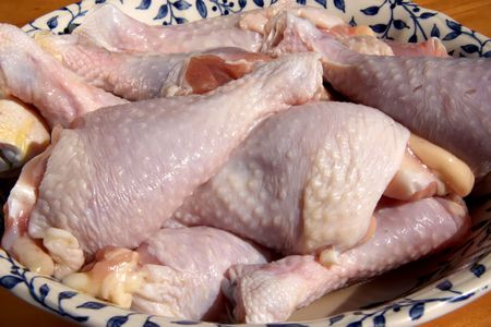 Raw chicken drumstick parts in pile in bowl photo