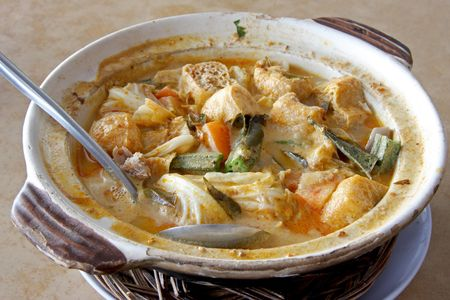 Fish head curry in clay pot traditional malaysian cuisine photo