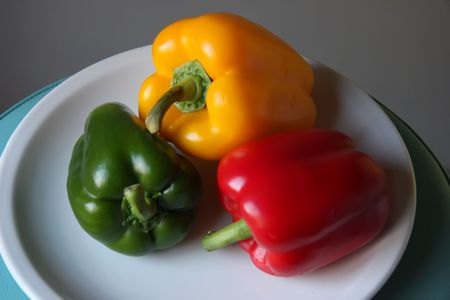 Several multicolored bell pepper capsicum vegetables on white plate photo