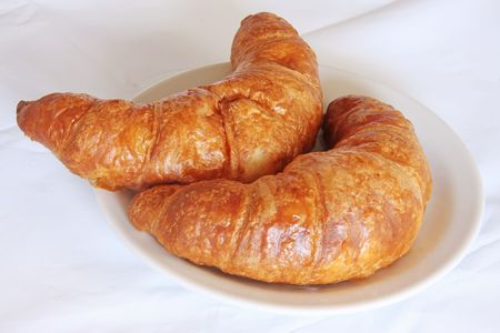 freshly: Freshly baked croissant french pastry bread on white plate