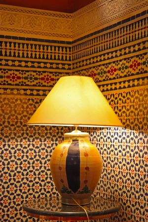 Traditional Moroccan ceramic lamp next to tiled walls photo