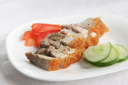 Chinese roast pork with crispy skin, sliced on plate photo