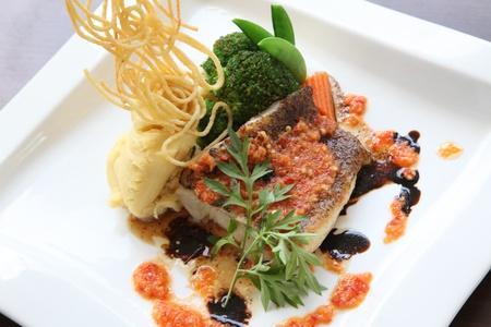 plato de pescado: Presentaci�n elegante de plato de pescado de mariscos de filete de lubina a la plancha