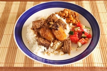 Asian Indian style beef curry on rice with two side dishes photo