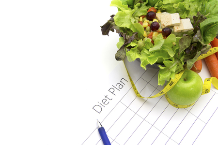 healthy eating, dieting, slimming and weigh loss concept - close up of diet plan paper green apple, carrot, measuring tape and salad