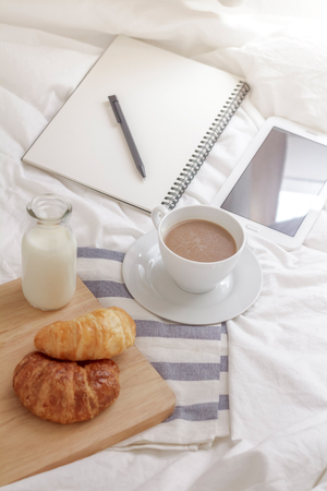 Simple workspace or coffee break in morning. cup of hot coffee, croissant and book on working table in the morning. Stock Photo