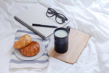 Simple workspace or coffee break in morning. cup of hot milk, croissant and book on working table in the morning.