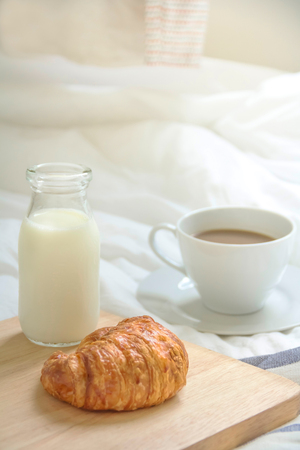 Bed breakfast with coffee cup, croissants and milk in bed, cozy relaxing morning coffee, holidays and winter concept