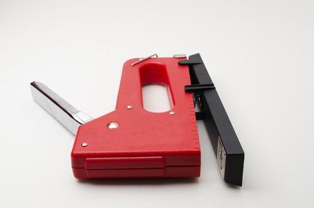 Grapadora roja Gun.shoot sobre fondo blanco. �til para la oficina y el hogar. Administrar y combinar documentos.