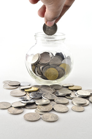 dime: Inserting Malaysian Coin in glass container. Shoot over white background. Focus on the important part. Shallow depth of field. Stock Photo