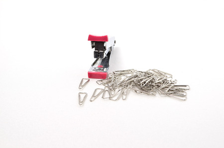 Paperclips and Stapler. Shoot over white background. Focus on the closes distance. Shalow depth of field. Stock Photo