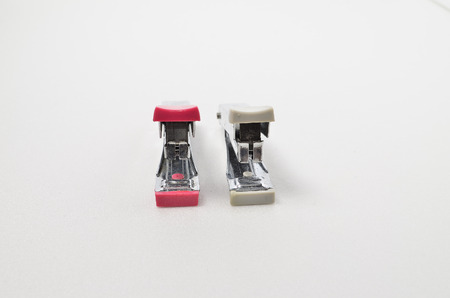 Pink and Grey stapler. Shoot over white background. Focus on the closes distance. Shallow depth of field. Stock Photo