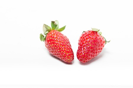 Strawberries over white background. Focus on the important part. Shallow depth of field. Stock Photo