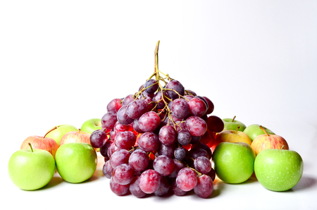 field depth: Red And Green Apples with grapes shoot over white background. Shallow depth of field. Focus on the closes distance. Stock Photo