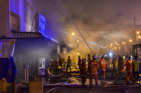 fireman with hose: Kedah, Malaysia - March 8, 2015 : A supermarket was burned terribly and almost 10 Fireman vehicle come to resque and stop the fire. The water was supplied from one kilometre away by Fireman Hose.