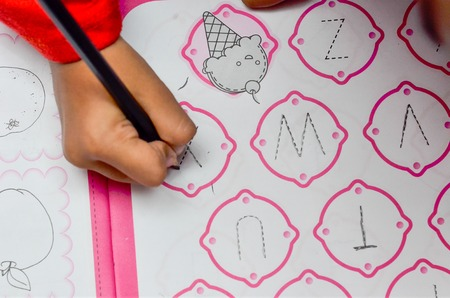 learning by doing: Kids learning to write letter by doing homework using pencil