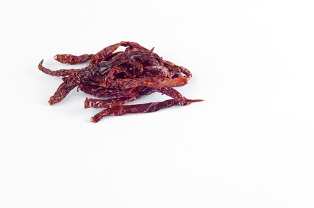 usually: Dried red chili on white background. Usually use in spicy cooking or spicy taste.
