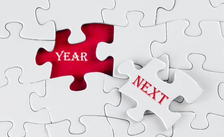 next year: Business Concept - White puzzle with red void in the middle when one piece of the puzzle is taken out with word Next Year