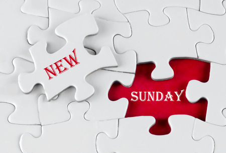 White puzzle with void in the middle when one piece of the puzzle is taken out with text written New Sunday Stock Photo