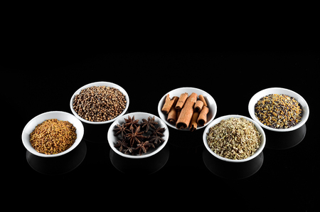 fenugreek: Mix Spice anise aniseed cinnamon fenugreek in white bowl over black background