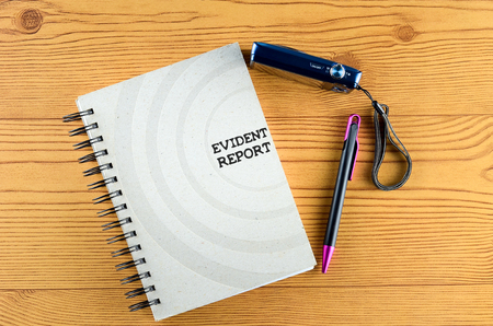 evident: EVIDENT REPORT written on book. Office desk with  ring book, pen, and camera concept