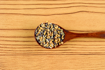 Mixed Fenugreek Spice in wooden spoon over wooden background
