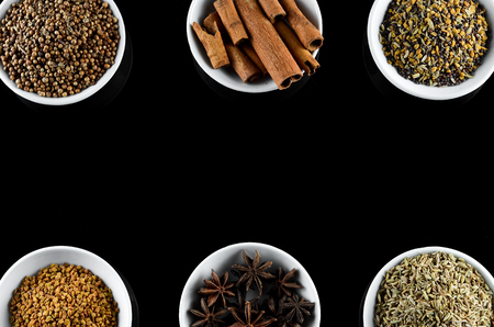 Mix Spice anise aniseed cinnamon fenugreek creating frame with space for text in white bowl over black background