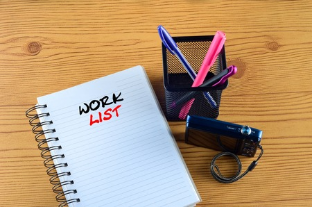 WORK LIST written on book. Office desk with  ring book, pen, and camera concept Stock Photo