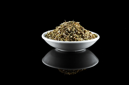 aniseed: Aniseed Spice in white bowl over black background Stock Photo