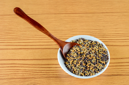 Mixed Fenugreek Spice in white bowl with wooden spoon over wooden background
