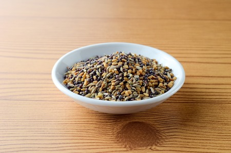 Mixed fenugreek spice in bowl over wooden background