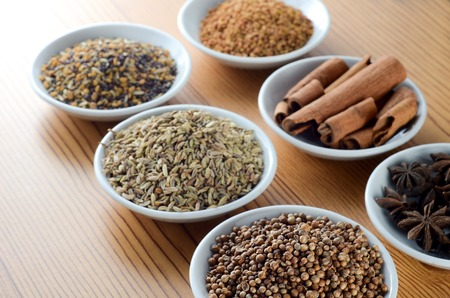Mixed spice anise, aniseed, cinnamon, fenugreek in bowl over wooden background Stock Photo
