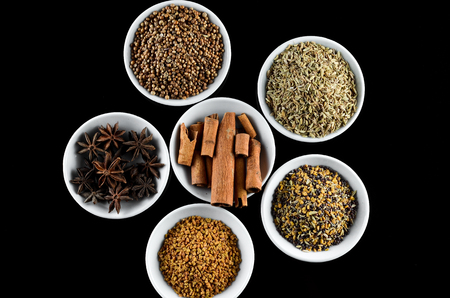 asian flavors: Mix Spice anise aniseed cinnamon fenugreek in white bowl over black background