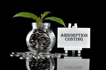 Business Concept - Money in glass container with tree and white board written Absorption Costing