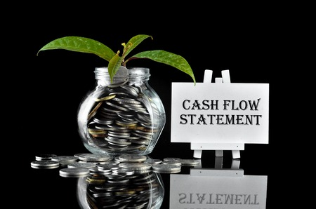 Business Concept - Money in glass container with tree and white board written Cash Flow Statement