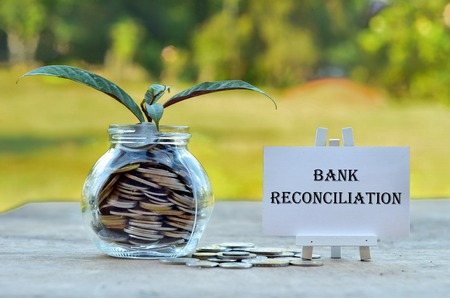 Business Concept - Money in glass container with tree and white board written Bank Reconciliation