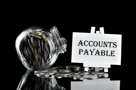 accounts payable: Business Concept - Money in glass containe and white board written Accounts Payable