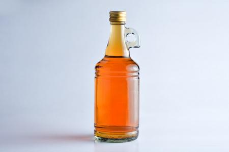 Apple Cider Vinegar in a glass bottle over white background