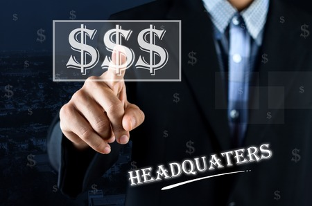 headquaters: Business man pointing hand on transparent money symbol with text written Headquaters Stock Photo