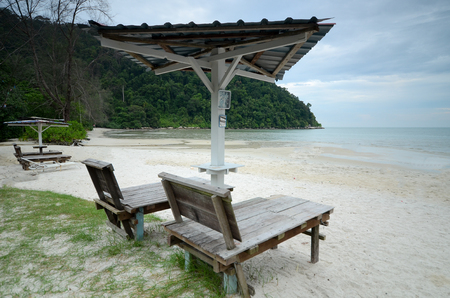 Sun loungers on the beach with wooden chair and umbrella