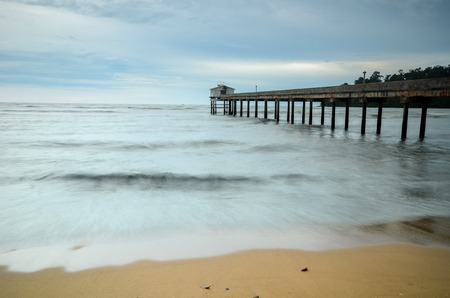 overcast: Beautiful Beach with jetty structure to ocean on overcast day