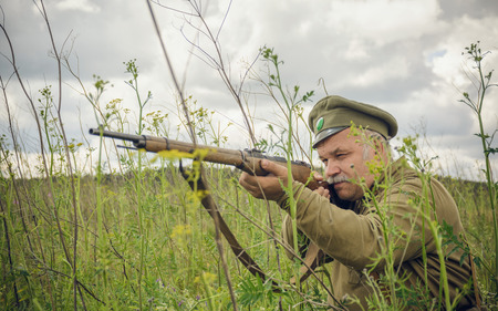 antique rifle: POKROVSKOE, SVERDLOVSK OBLAST, RUSSIA - JULY 17, 2016: Historical reenactment of Russian Civil war in the Urals in 1919. Soldier Of The White Army