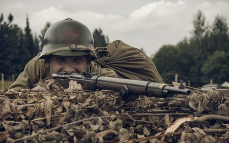 reenacting: PERM, RUSSIA - JULY 30, 2016: Historical reenactment of World War II, summer, 1942. Soviet soldier with rifle