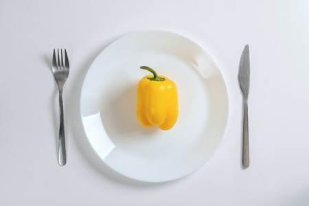 Knife, fork and yellow pepper, paprica on a white plate on a white background, top view