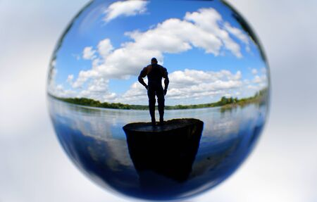 A silhouette of a man standing on a cliff at a lake, captured through a crystal lens ball