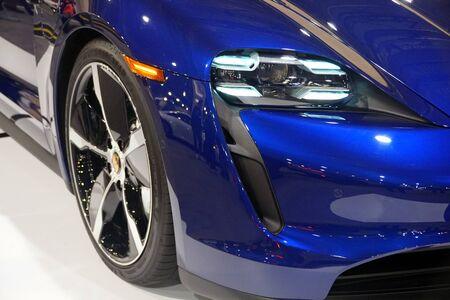Philadelphia, Pennsylvania, U.S.A - February 9, 2020 - The headlights of the blue metallic 2020 Porsche Taycan 4S all electric sports sedan